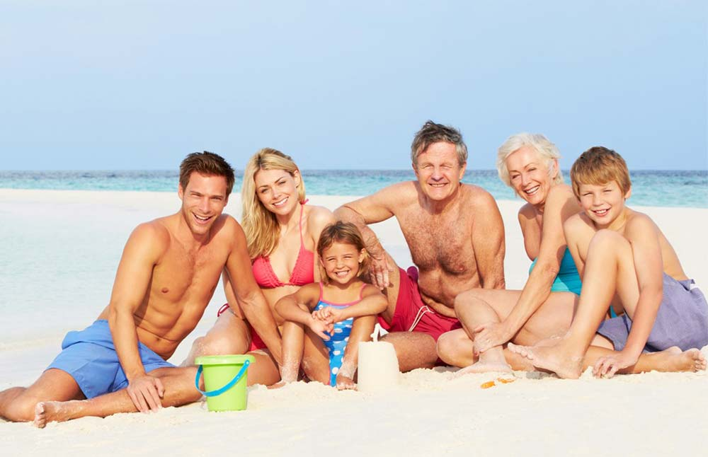 Healthy family sitting and smiling at the beach