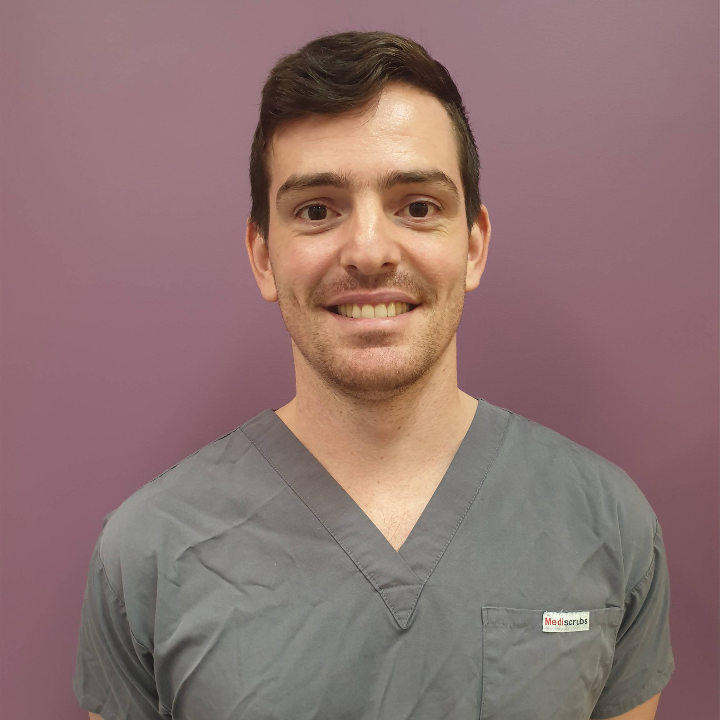 Portrait image of Dr Jack Gilpin wearing Mediscrubs smiling