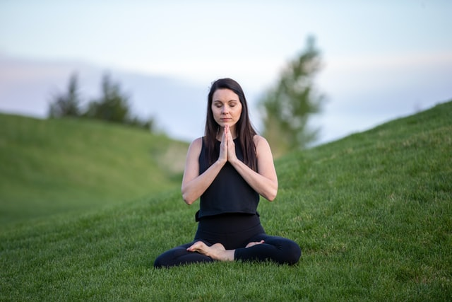 Woman seated on grassy mountain with legs crossed and hands in a Yoga - meditation position
