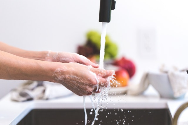 Hands being washed with soap prior to food preparation to prevent the spread of germs