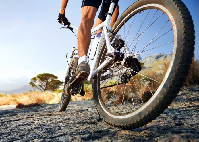 A guy cycling in the woods to more active to reduce the risk of kidney disease